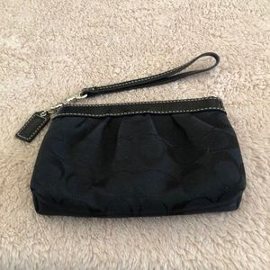 Coach wristlet in black with red lining.
